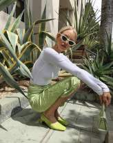 a girl wearing white sunglasses, a white top and a silky green skirt
