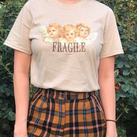 """A graphic tee that has three angels and says """"fragile"""""""