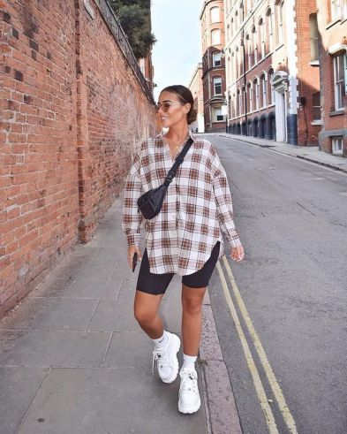denim shorts styled with an oversized flannel and a belt bag