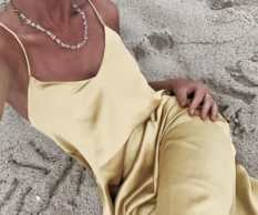a silk or satin slip dress in yellow on a sandy beach