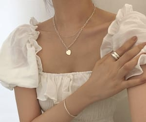 gold necklace and a white milkmaid top with puffy sleeves