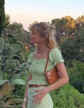 a girl wears a green milkmaid top in a garden